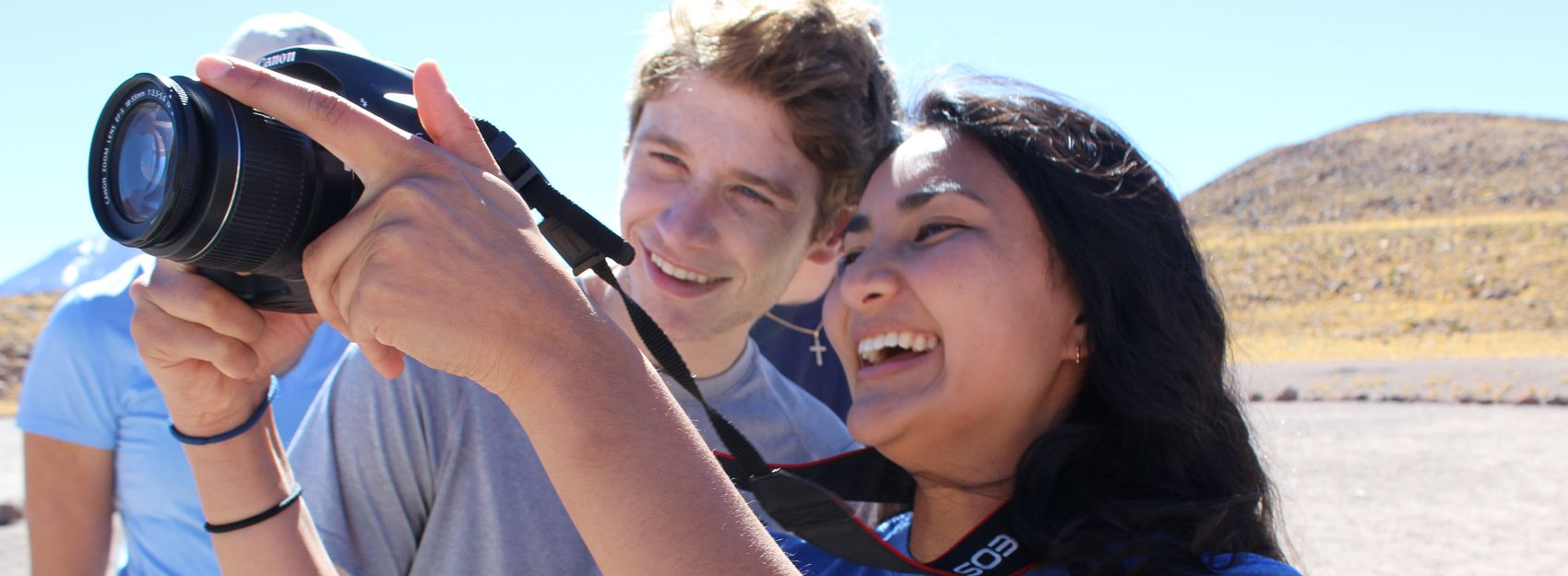 two students outside using camera
