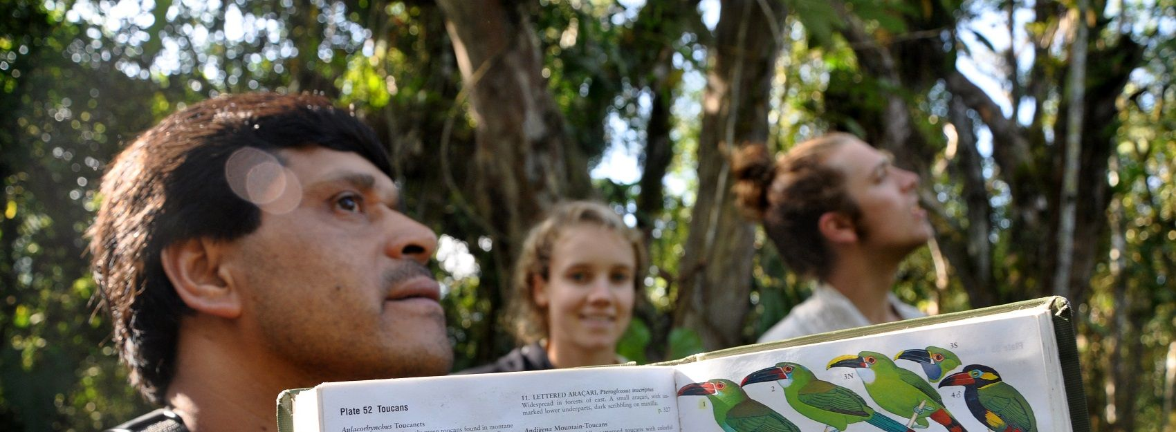 professor holding book of birds for class excursion in rainforest