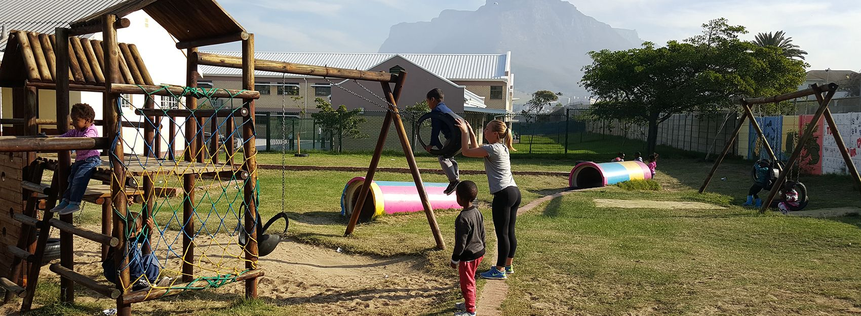 volunteer abroad student pushing children on a swing