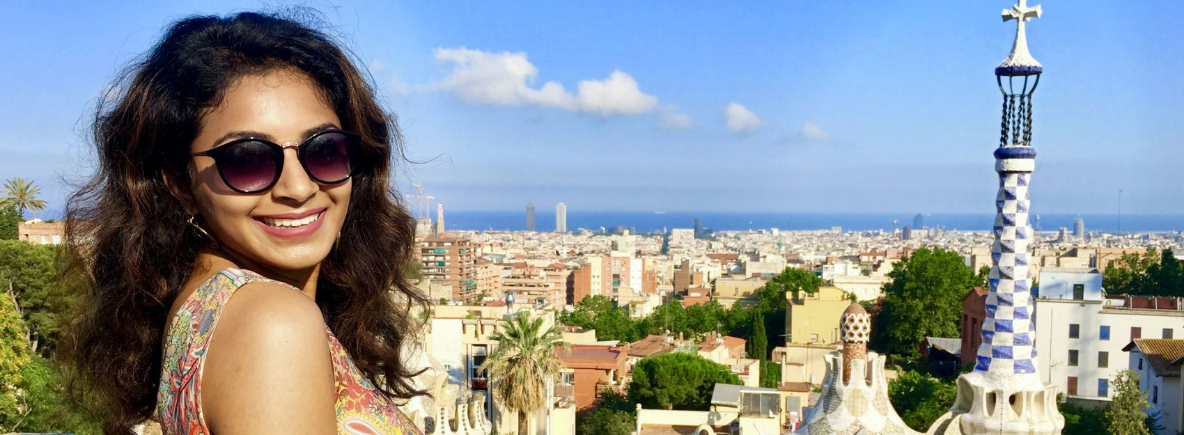 Student participating in an internship in Barcelona smiling over skyline
