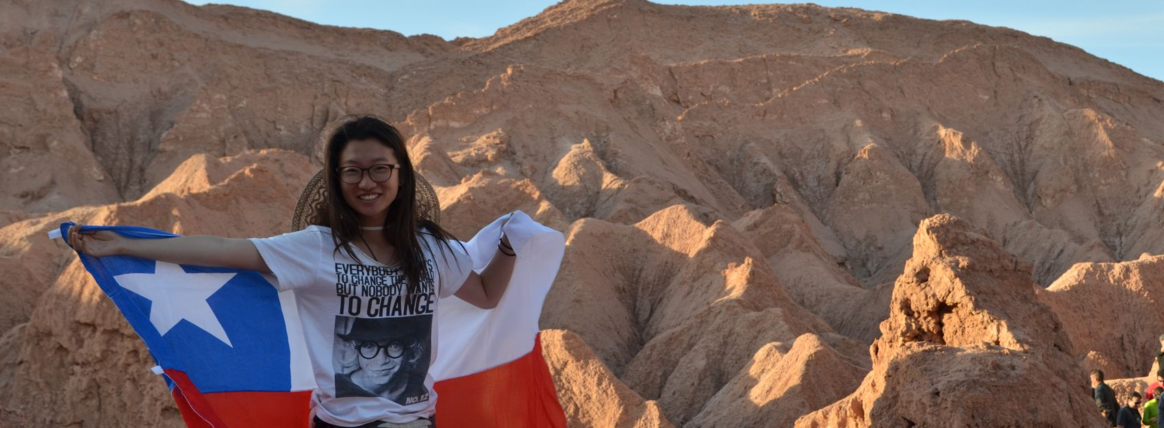 student posing with Chilean flag in front of red rocks