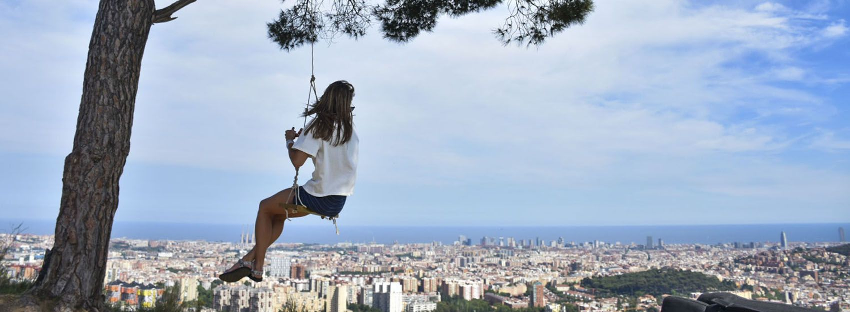 student on tree swing overlooking the city of Barcelona and the Mediterranean Sea