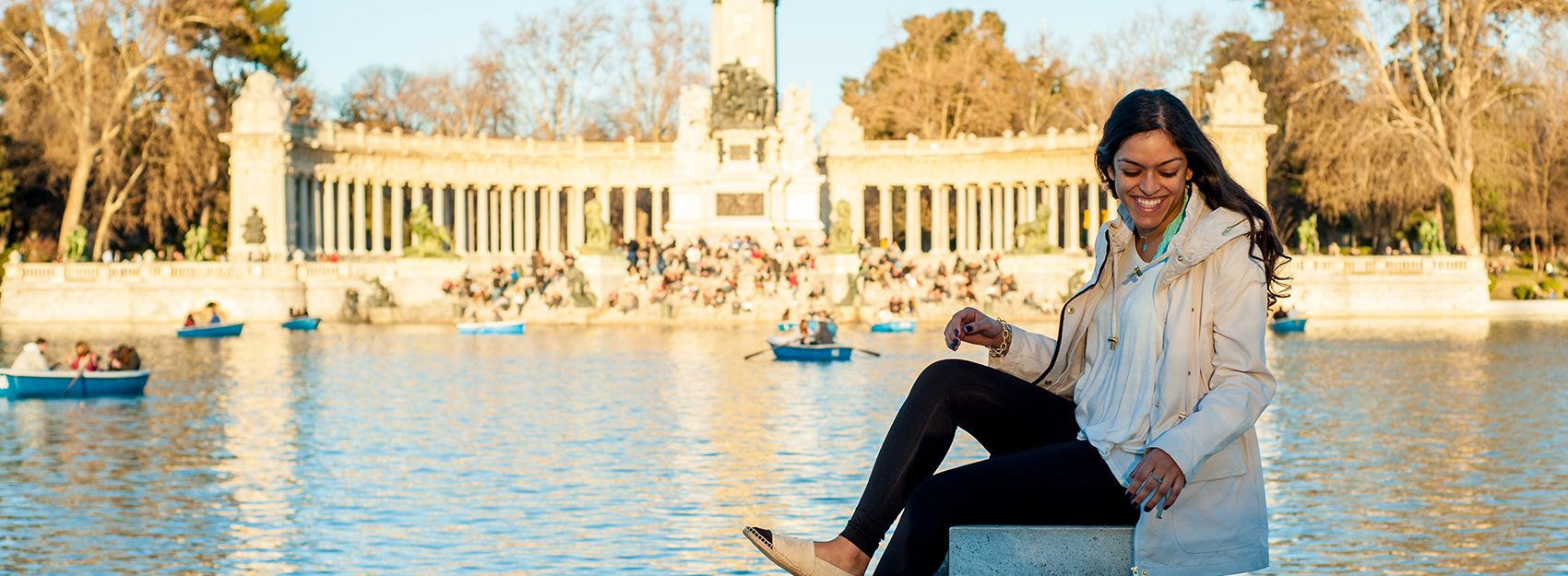 Madrid Study Abroad student sits on ledge at Retiro Park with pond and monument in the background