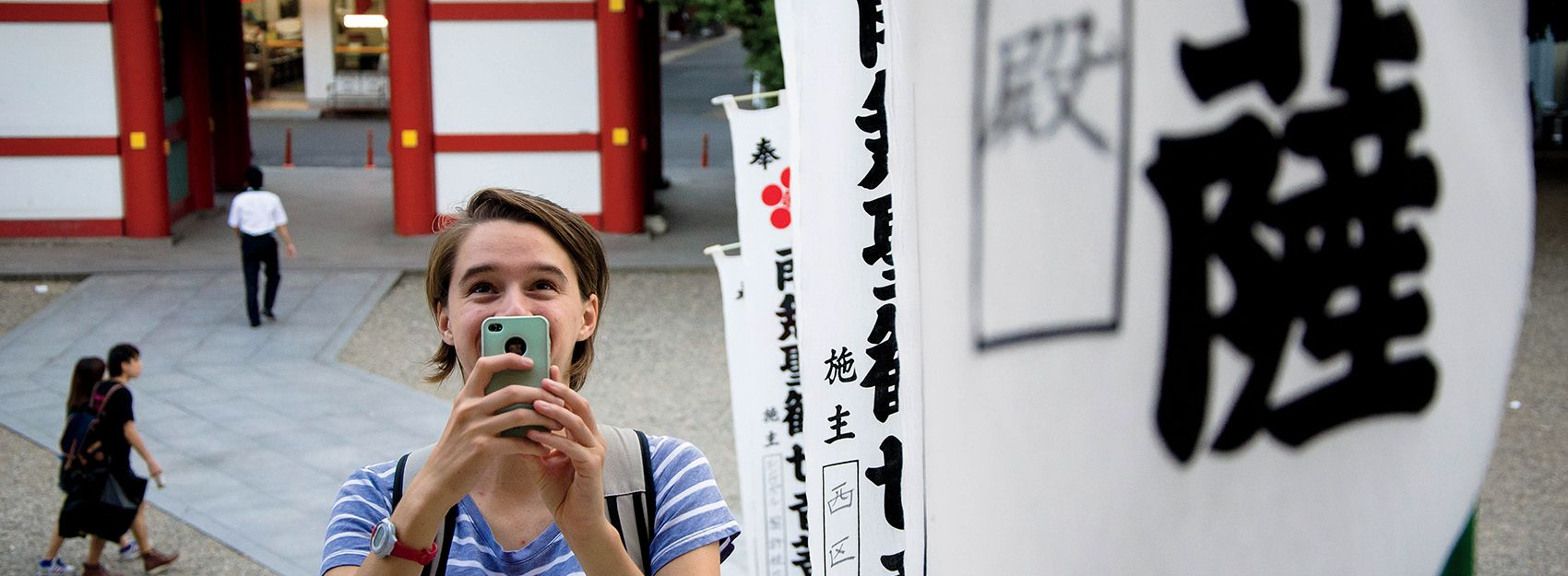 Nagoya Study Abroad student takes a photo next to calligraphy banners