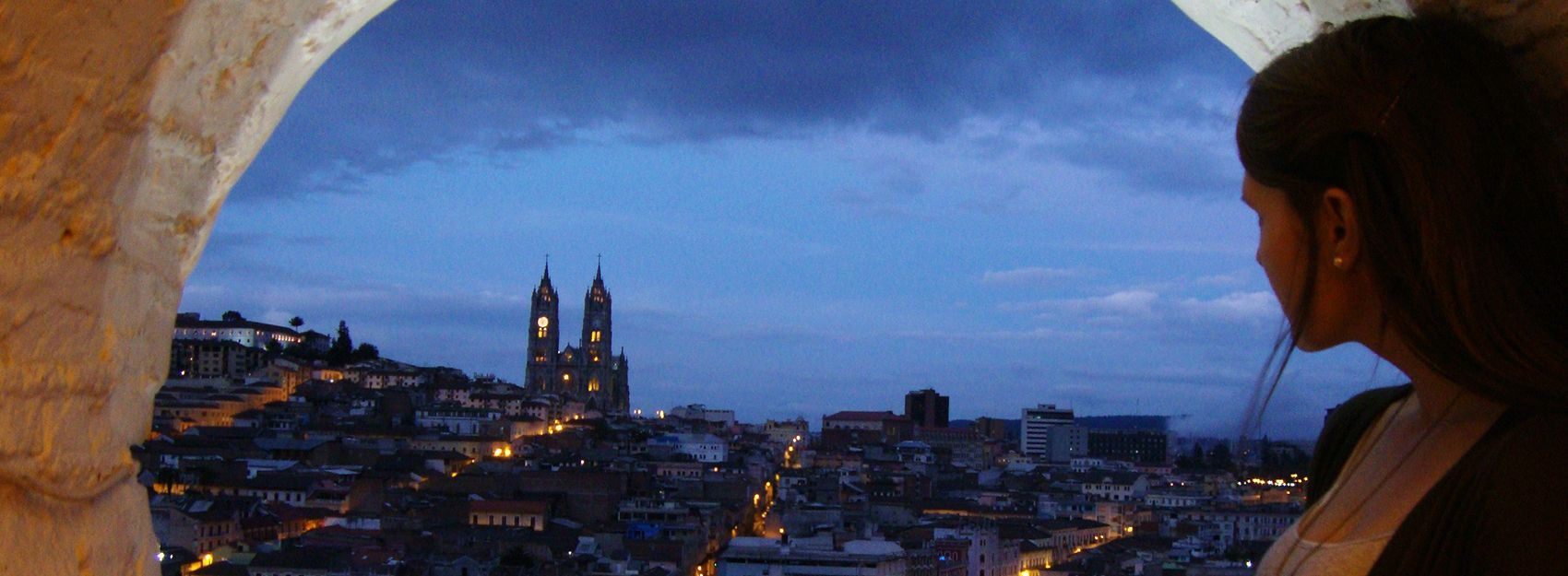 Quito study abroad student overlooking the city at night from a circular look out