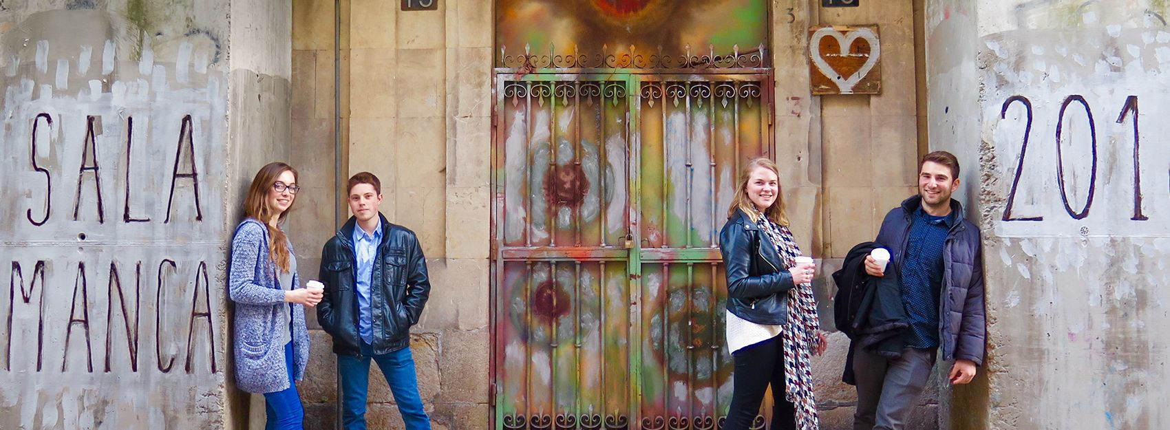 Salamanca study abroad students at a spray painted wall and gate along the street in Salamanca, Spain