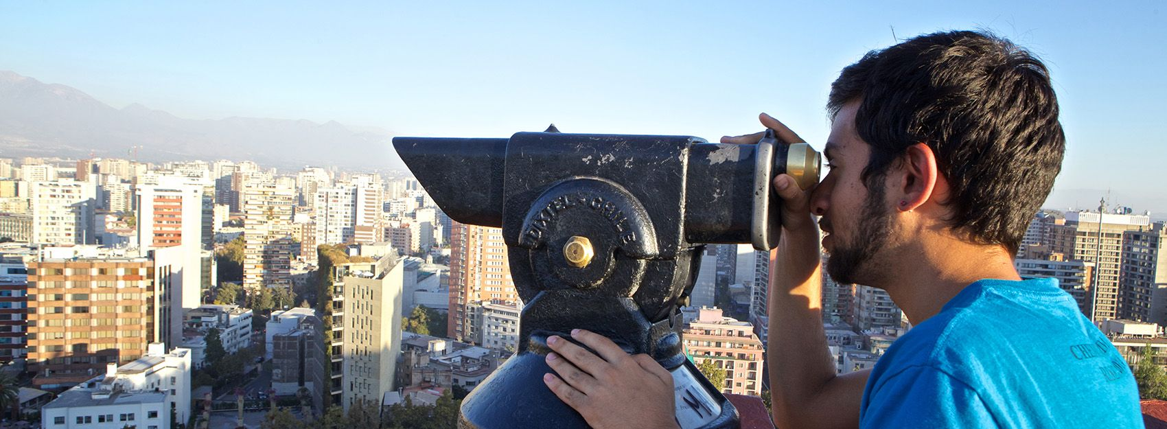 Santiago study abroad student looks through a tower viewer at an overlook above the city