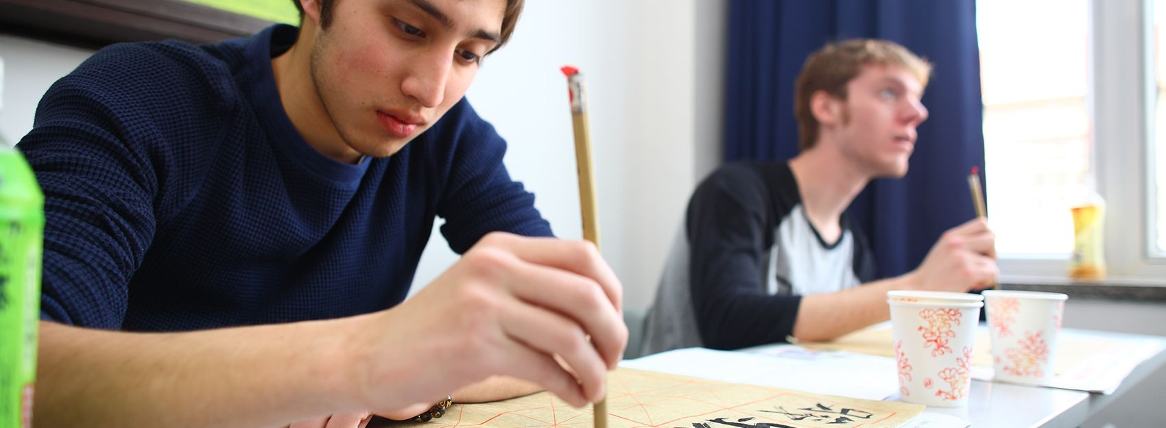 A Shanghai study abroad student practices calligraphy in class