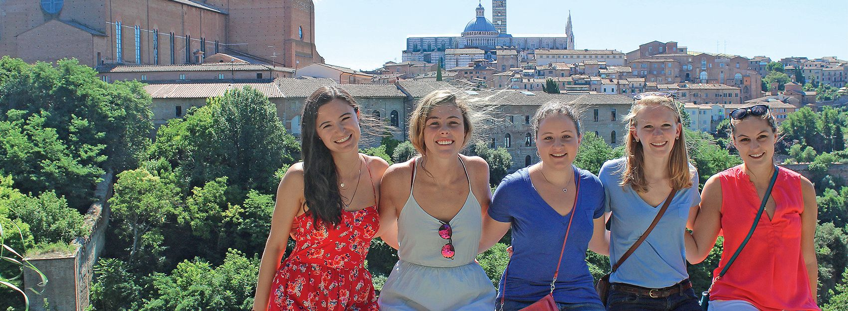 Siena Study Abroad students sit on a railing with the city and cathedral in the background