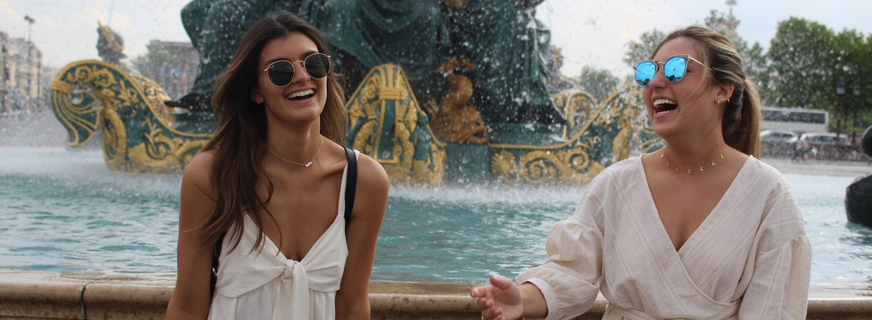 two students laughing and throwing a coin in a fountain at place de la concorde in paris, france