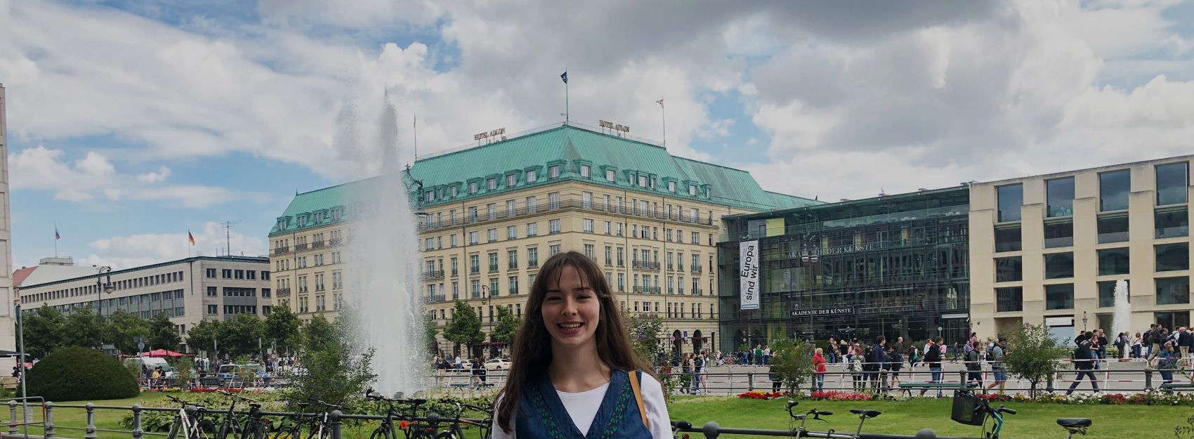 female intern abroad in berlin, smiling in front of a building