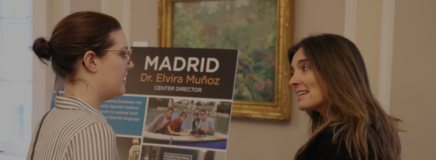 two women talking in front of a poster board about Madrid