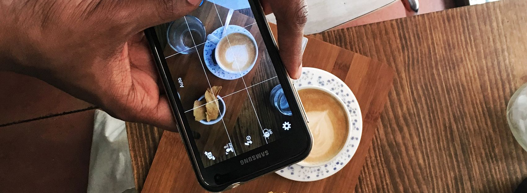 hands holding a phone taking a photo of a cup of coffee