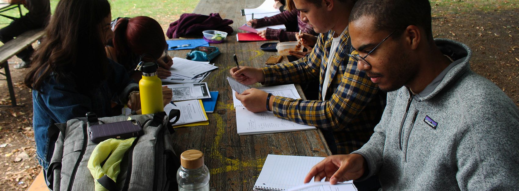 Students studying on picnic bench outside