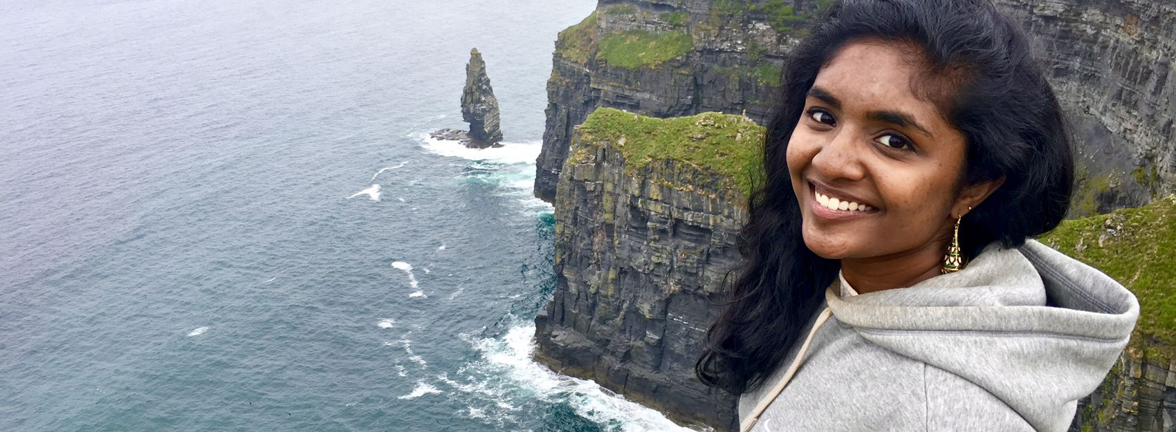 student standing smiling on the cliffs of moher in ireland
