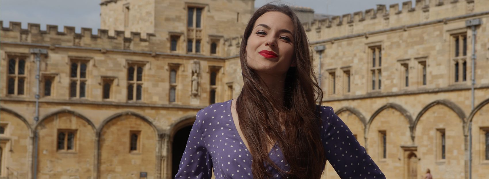 Student in blue dress standing confidently in front of Oxford University's Christ Church College