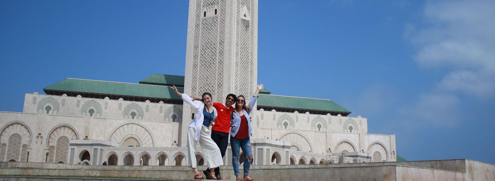 students posing in front of tower in casablanca, morocco