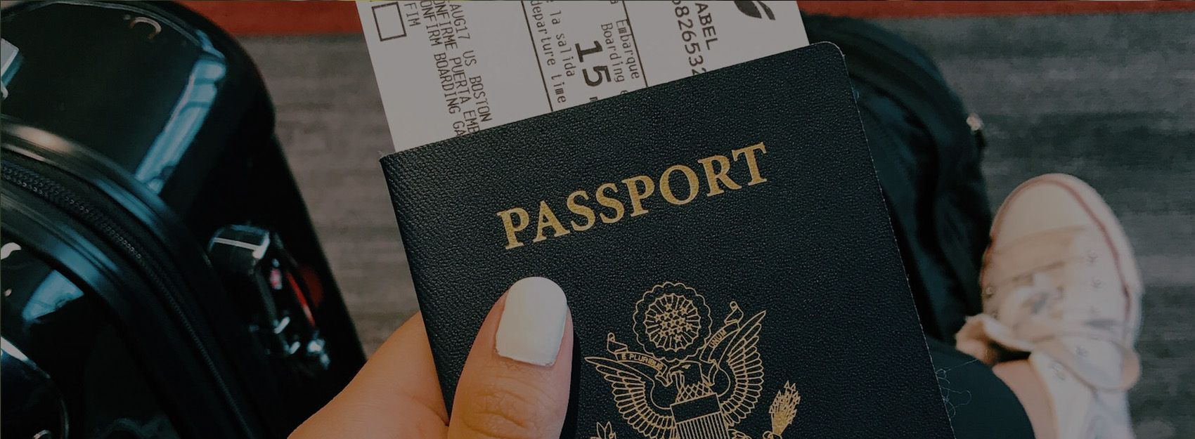 hand with white painted nails holding passport and boarding pass with suitcase in background