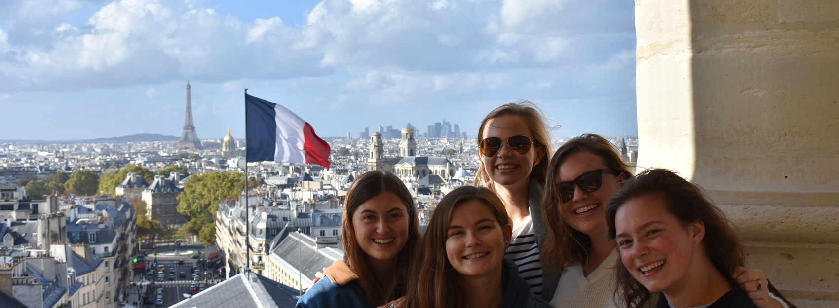 group of IES Abroad students with the french flag and eiffel tower in the background