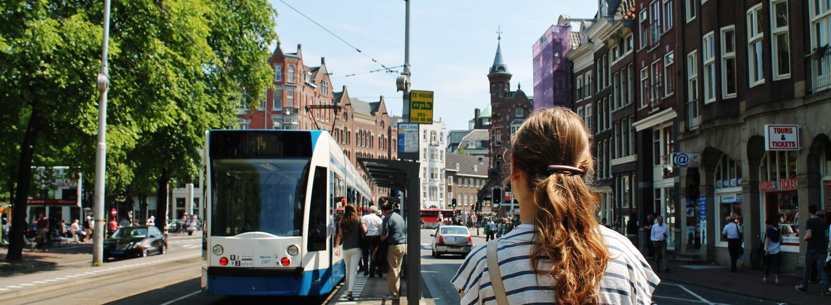 student walking down street in Amsterdam near a train line