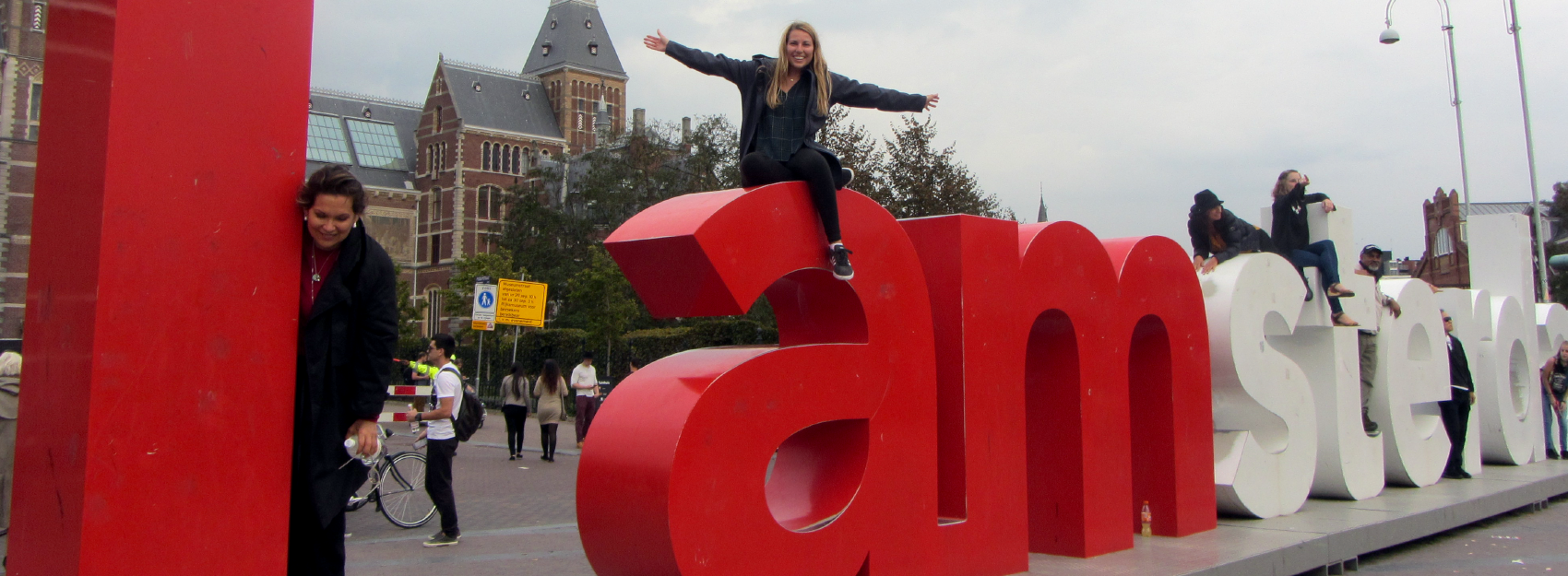 students sitting on I amsterdam sign