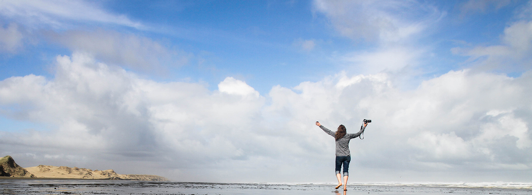student holding camera standing with arms outstretched at the beach