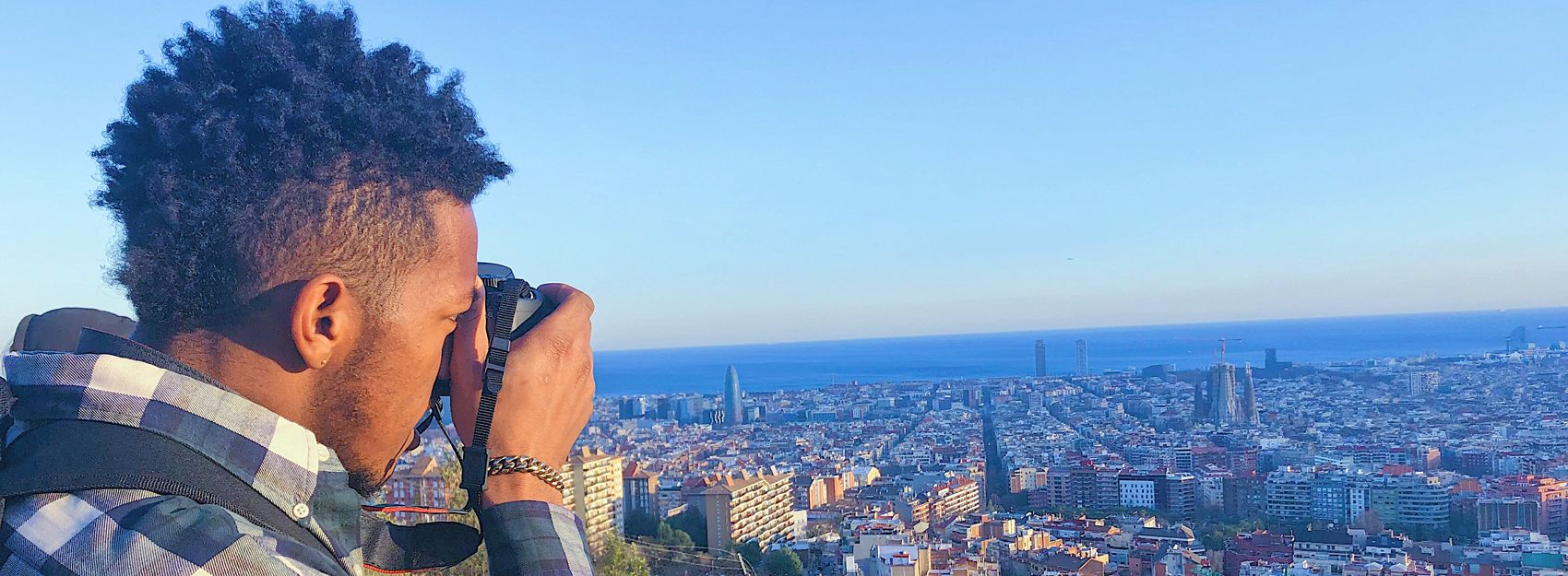 Male student taking photo of Barcelona cityscape and ocean