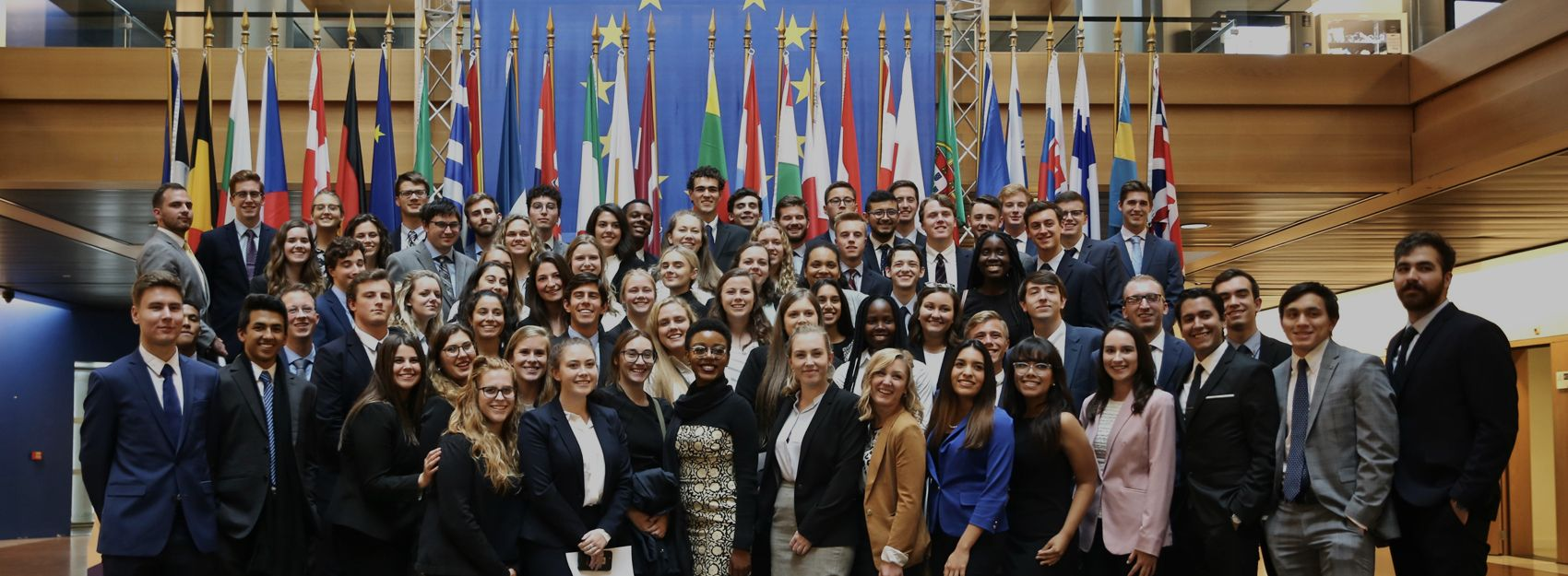 group of students standing in front of European country flags at EU Parliament