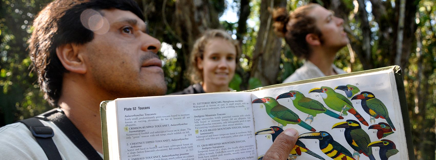 Man holding book about birds pointing at page