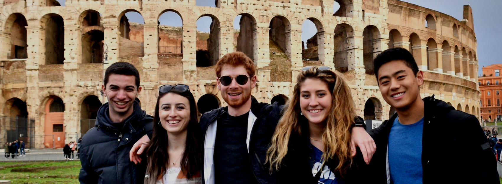 students smiling standing in front of colosseum