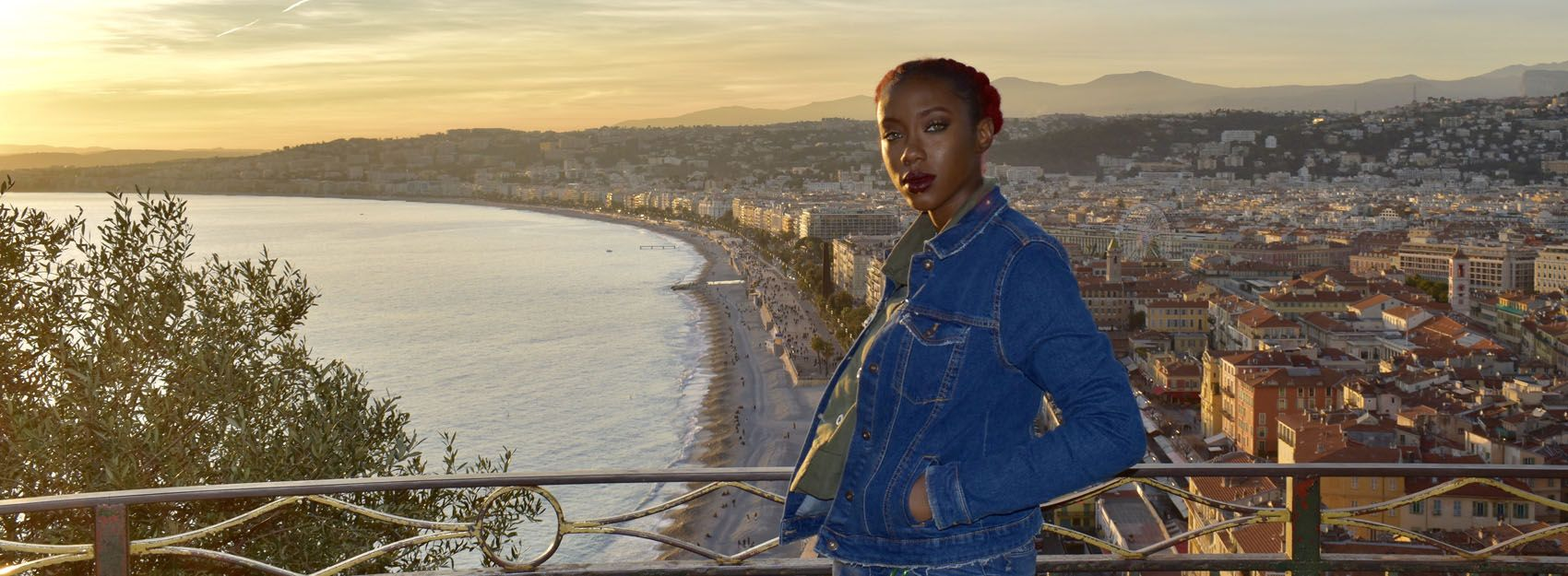 student wearing denim jacket standing overlooking Nice shoreline
