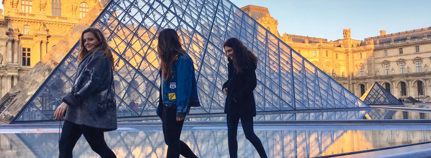 three students walking next to the glass pyramid of the Louvre in Paris, France