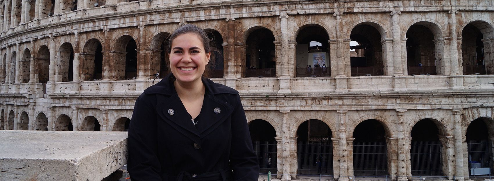 student standing in front of Colloseum