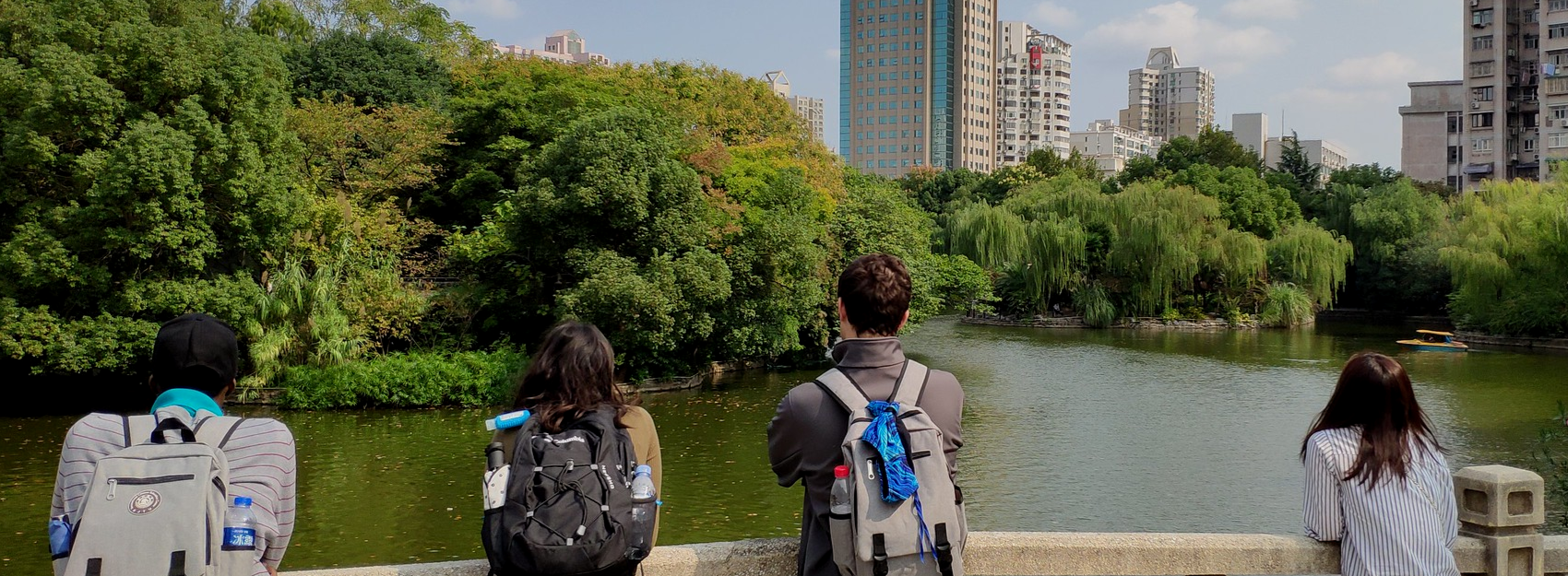 4 students with backpacks overlooking water at park in shanghai
