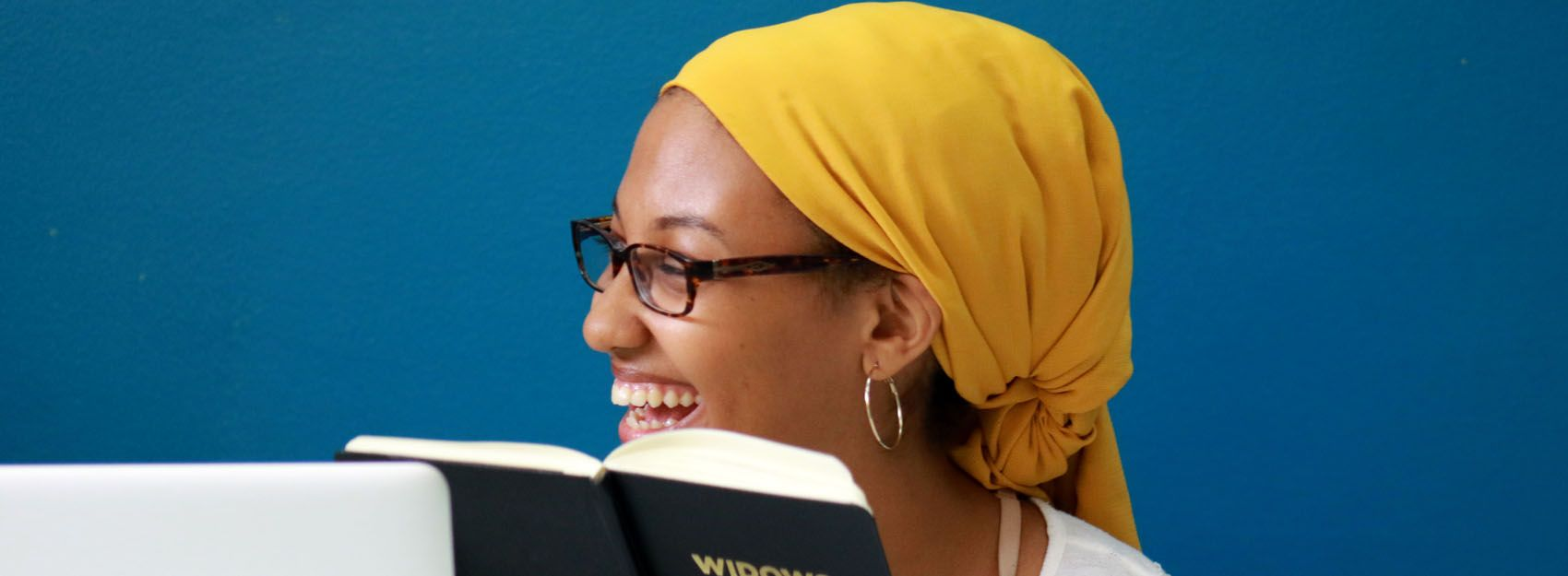 student with yellow head scarf and glasses smiling and holding book
