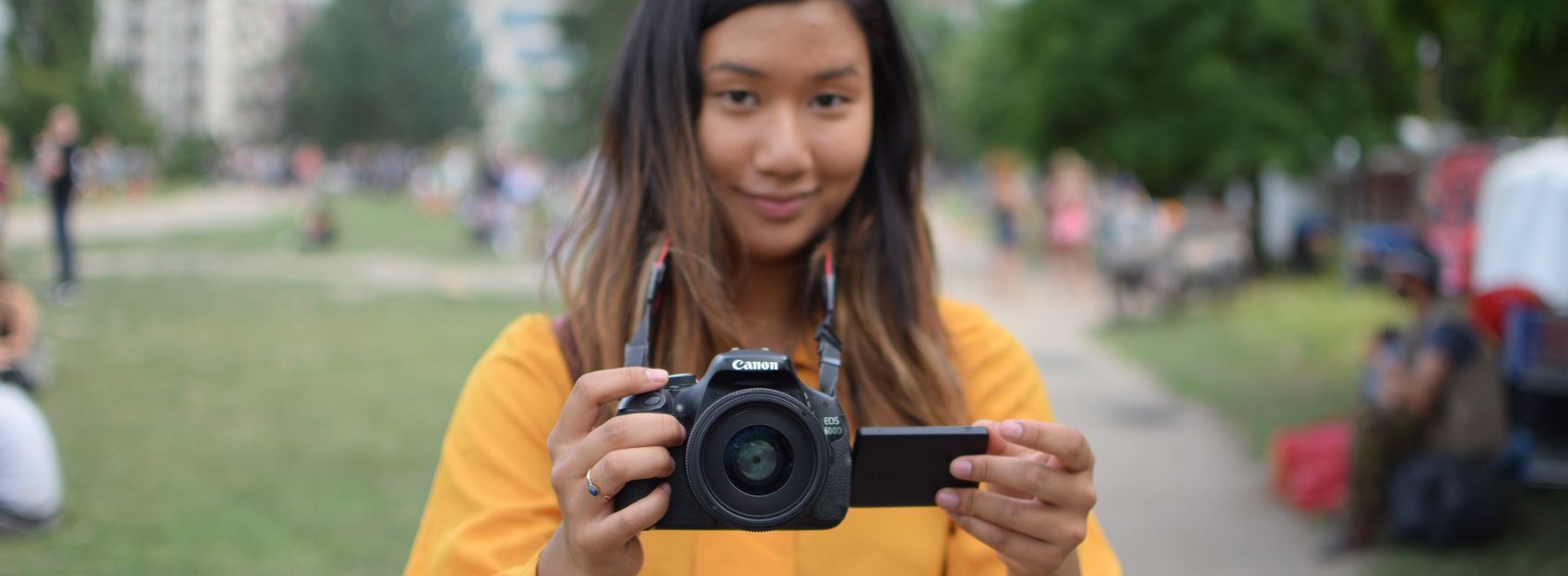 student in yellow shirt holding a camera