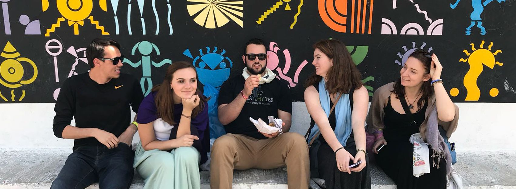 spanish study abroad students sitting in front of wall painted black with colored icons