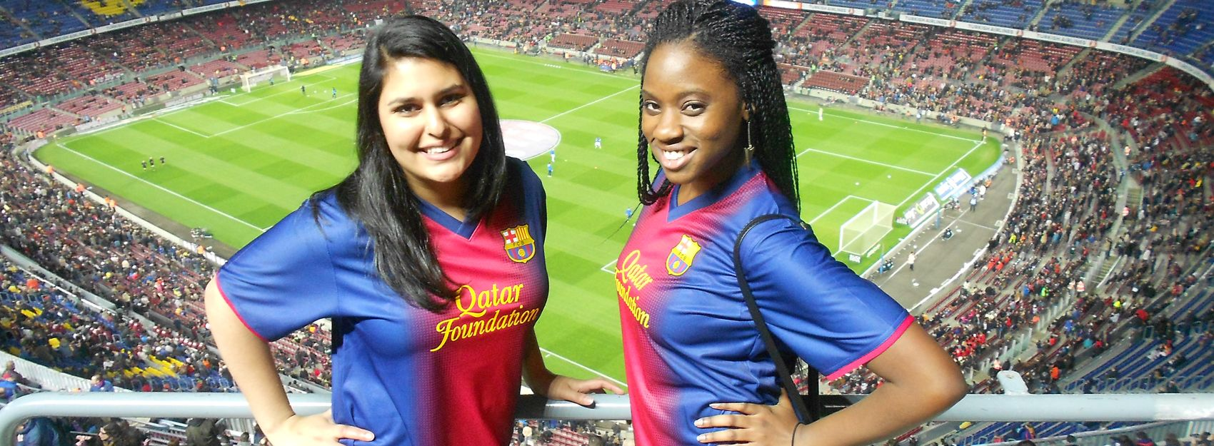 Two interns in stands at soccer stadium posing in jerseys