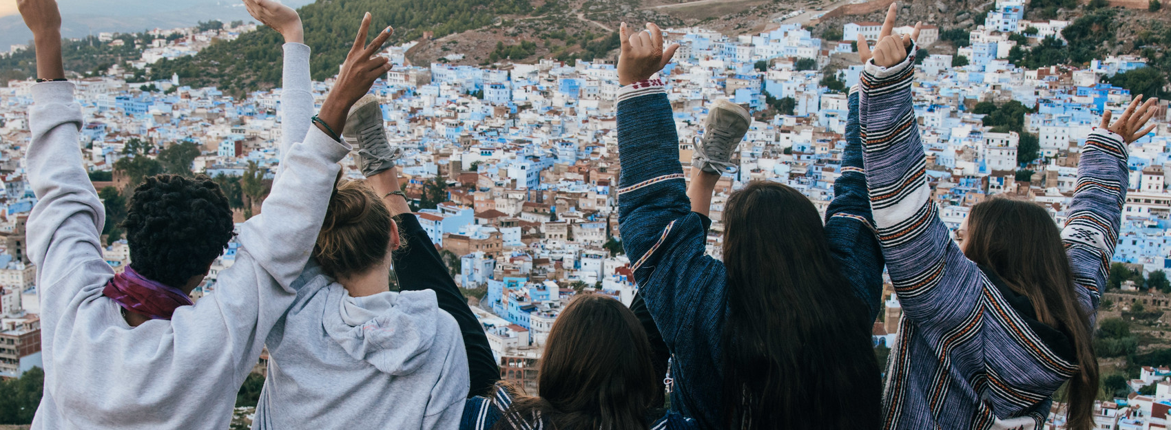 students with arms raised looking out at landscape