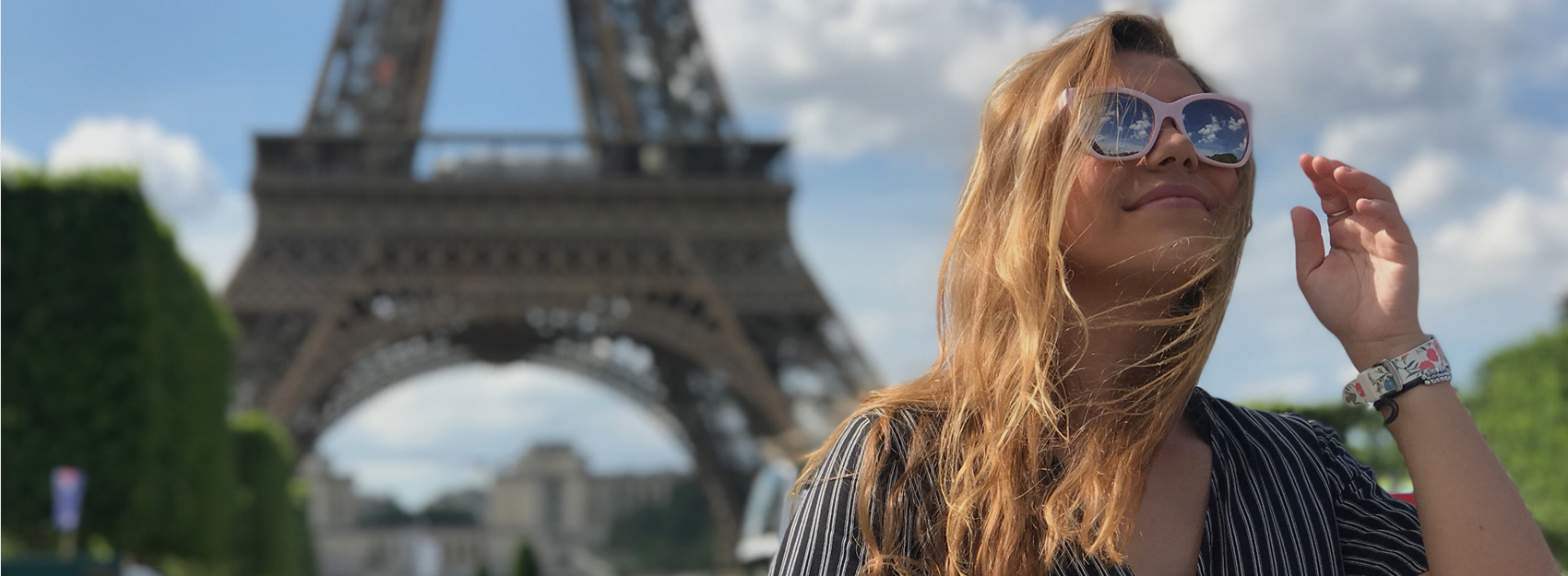 summer study abroad student wearing sunglasses in front of the eiffel tower