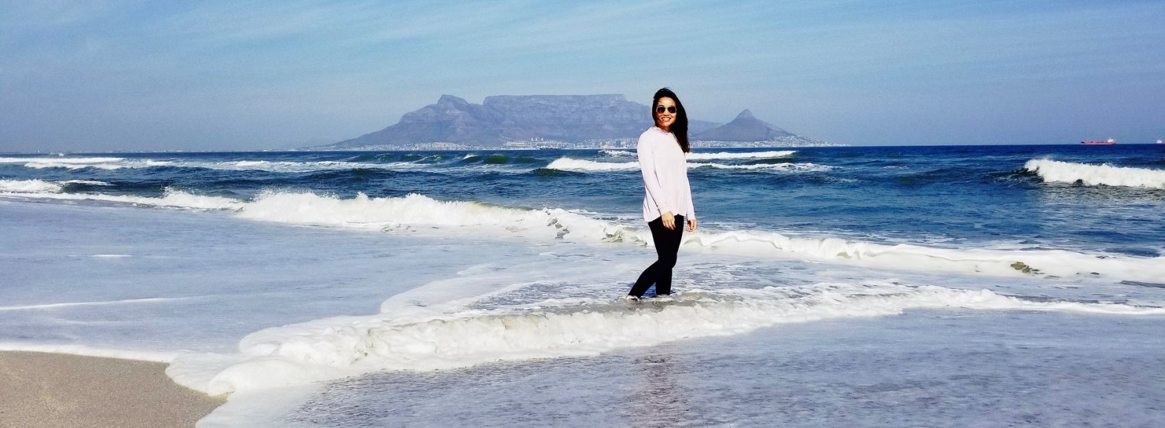 A student stands in the waves of a beach in Cape Town