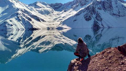 landscape photo of Collin squatting and staring off into the not-so-far distance past a lake where he sees two snowy mountains