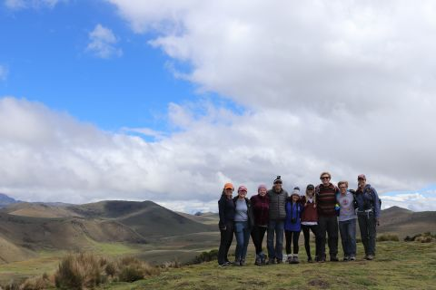 a group of students stand in front of mountains and the sky