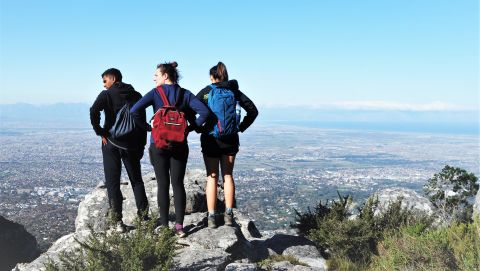 three students standing on a mountaintop overlooking Cape Town