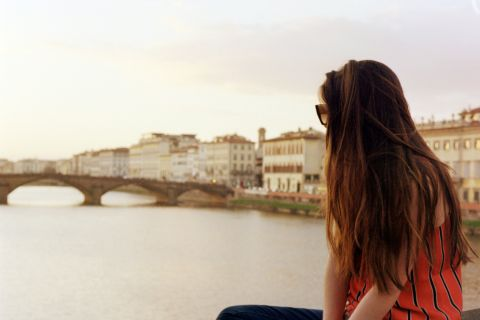 A girl with long brown hair sits overlooking a bridge on a river