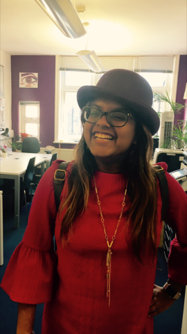 Headphot of Dayna smiling with glasses and a hat