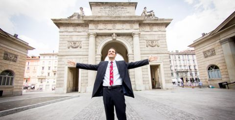 student in front of buildings in milan with outstretched arms
