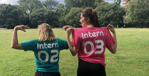 Two interns with their backs to the camera wearing t-shirts that say 'intern' on the back