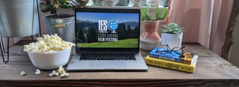 """Desk in front of window with Laptop Screen reading """"IES Abroad Study Abroad Film Festival"""", a bowl of popcorn, and books"""