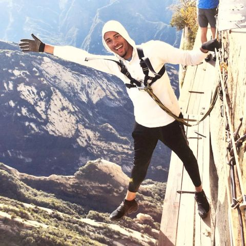 Terrence, clad in protective gear, hangs off the side of a mountain